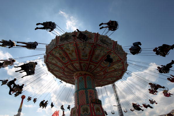 MUNICH, GERMANY - SEPTEMBER 19: Visitors of the Oktoberfest are silhouetted as they ride a merry-go-round during day 2 of the Oktoberfest at Theresienwiese on September 19, 2010 in Munich, Germany. 2010 marks the 200th anniversary of Oktoberfest.The Oktoberfest tradition started in 1810 to celebrate the October 12th marriage of Bavarian Crown Prince Ludwig to the Saxon-Hildburghausen Princess Therese. The citizens of Munich were invited to join in the festivities which were held over five days on the fields in front of the city gates. The main event of the original Oktoberfest was a horse race. The world's biggest beer festival will last this year from September 18 to October 4. (Photo by Miguel Villagran/Getty Images)