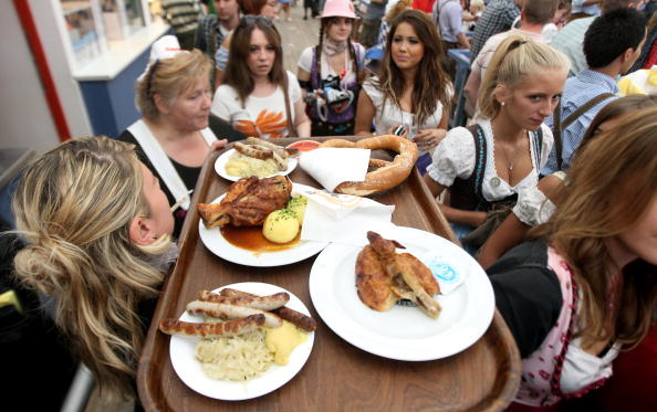 MUNICH, GERMANY - SEPTEMBER 19: A waitress carries a tray with different bavarian dishes through a group of visitors inside the Schottenhamel beer tent during day 2 of the Oktoberfest at Theresienwiese on September 19, 2010 in Munich, Germany. 2010 marks the 200th anniversary of Oktoberfest.The Oktoberfest tradition started in 1810 to celebrate the October 12th marriage of Bavarian Crown Prince Ludwig to the Saxon-Hildburghausen Princess Therese. The citizens of Munich were invited to join in the festivities which were held over five days on the fields in front of the city gates. The main event of the original Oktoberfest was a horse race. The world's biggest beer festival will last this year from September 18 to October 4. (Photo by Miguel Villagran/Getty Images)