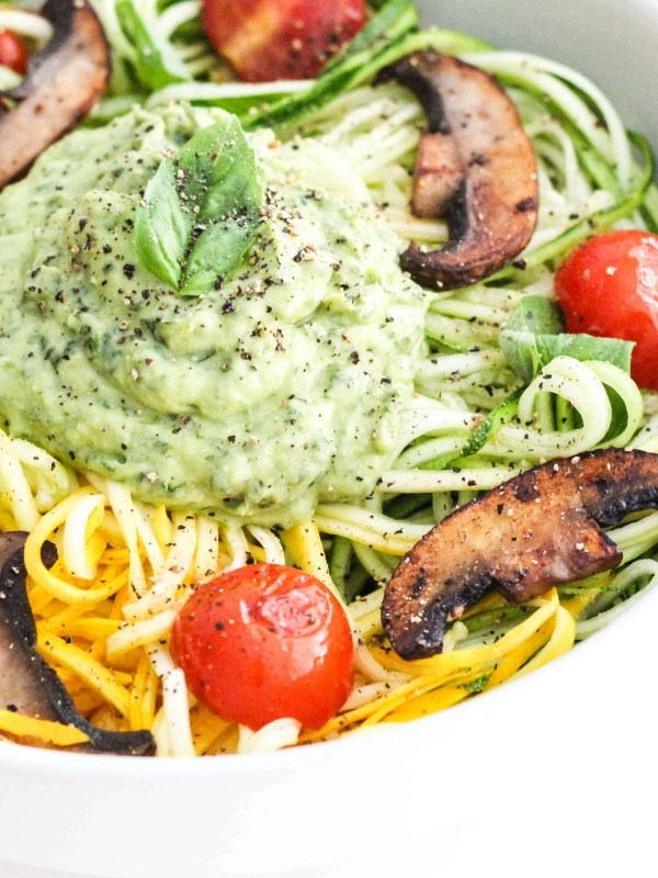 Zucchini noodles with creamy avocado pesto, sautéed mushrooms, tomatoes, and fresh basil