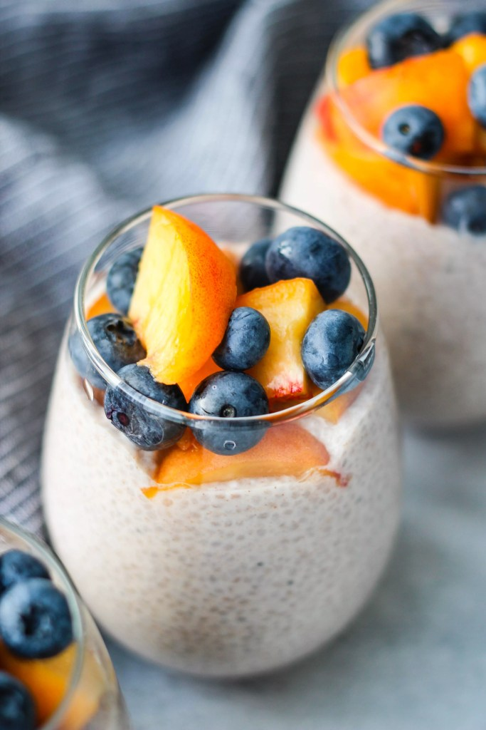 chia seed pudding topped with peaches and blueberries in glass jar