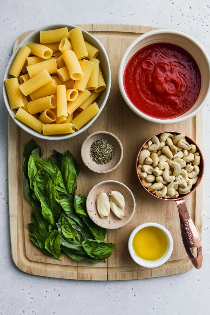 overhead photo of wood cutting board with bowls of ingredients for cooking pasta