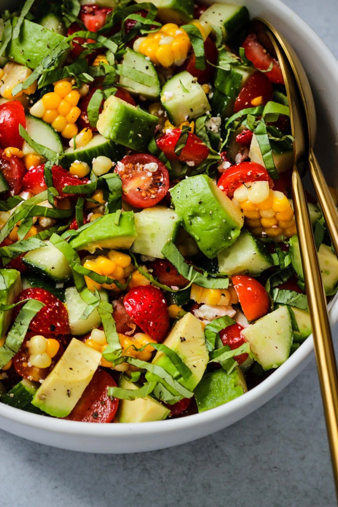 side angle shot of white bowl with corn, tomato, avocado, strawberry, basil, feta salad and gold serving spoons