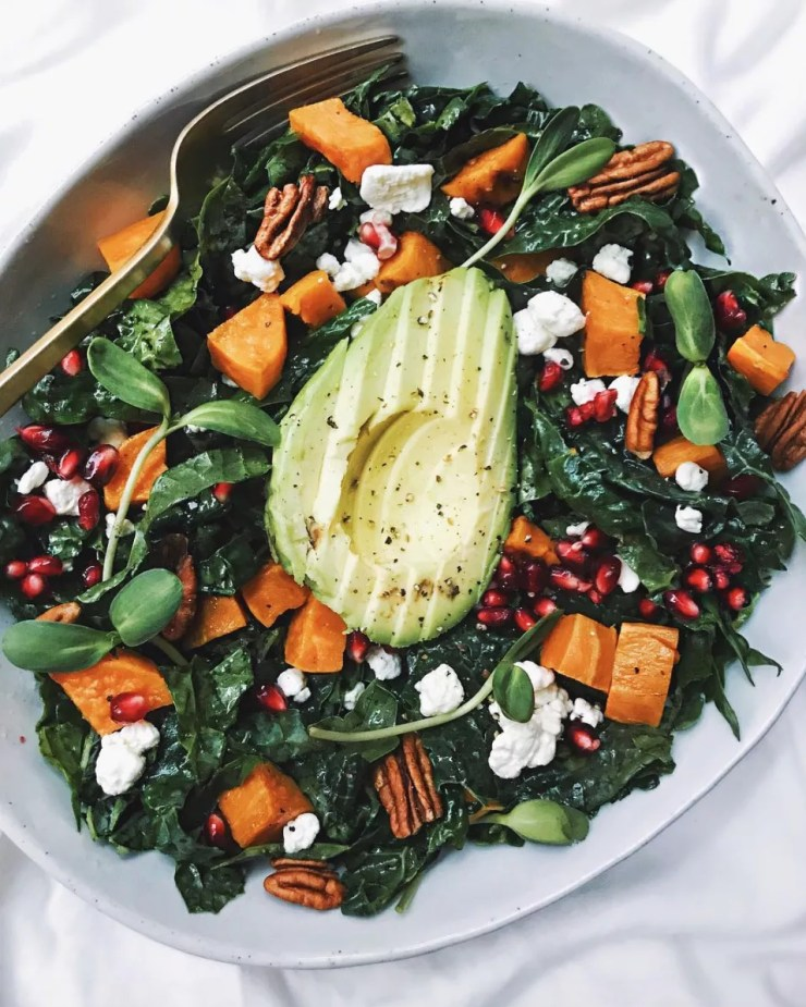 Massaged kale salad topped with roasted sweet potatoes, goat cheese, pomegranates, avocado, and pecans