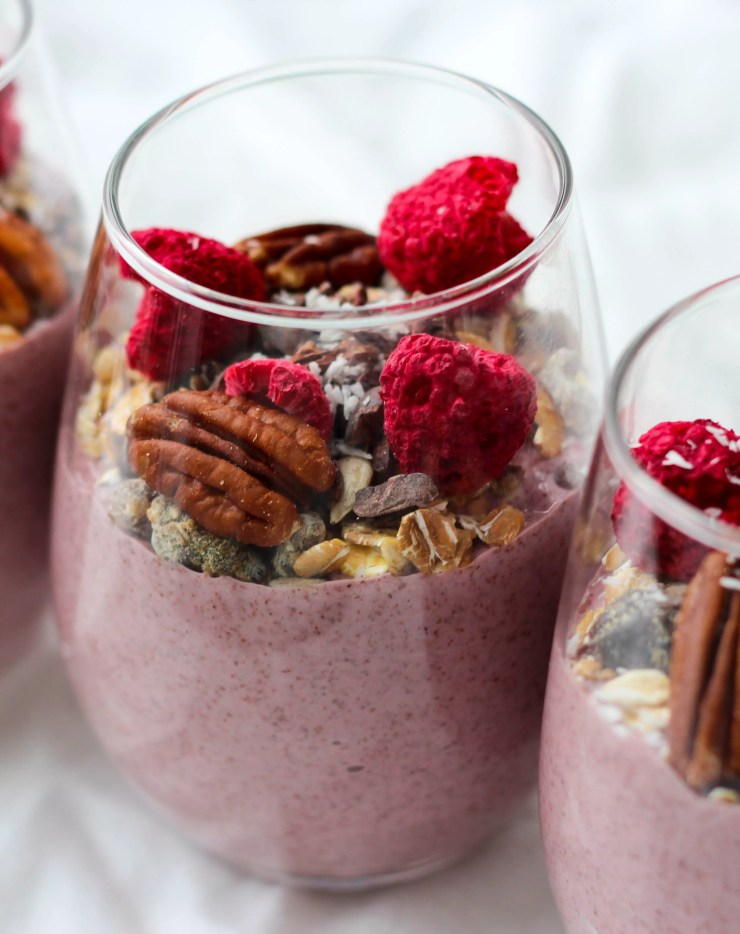 blended raspberry chia seed pudding topped with muesli, nuts, and seeds