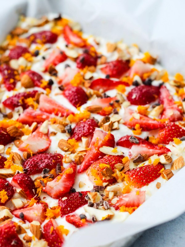 Baking sheet with frozen greek yogurt bark topped with chopped strawberries, orange zest, almonds, and cacao nibs