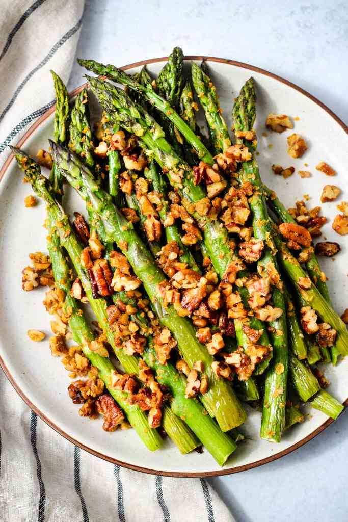 Roasted asparagus with chopped pecan parmesan on a white plate with a stripped dish towel