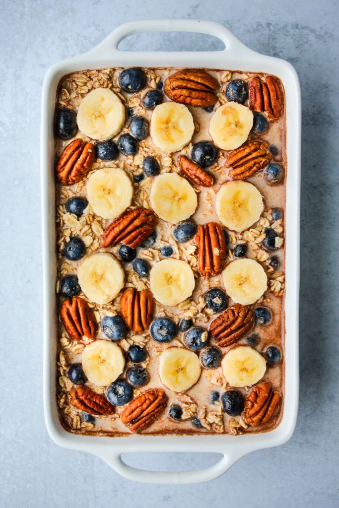 blueberry banana baked oatmeal with pecans in white baking dish