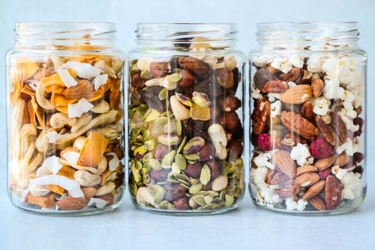 three glass jars with different homemade trail mix ingredient combinations