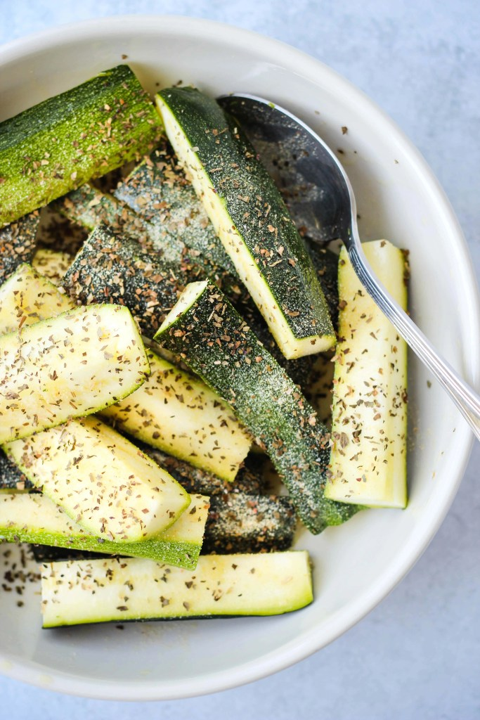 zucchini in a bowl with dried basil
