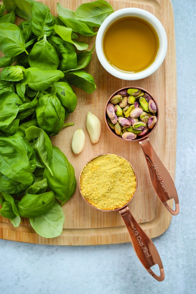 fresh basil, garlic, olive oil, pistachios, and nutritional yeast on a wooden cutting board