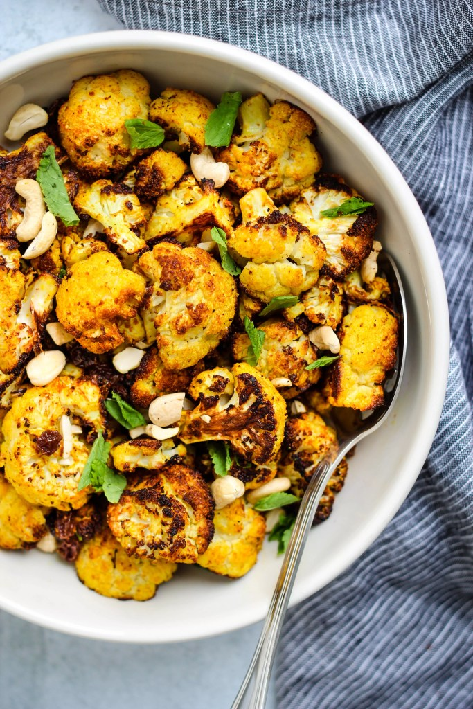 white bowl of curry-roasted cauliflower with mint, cashews, and raisins