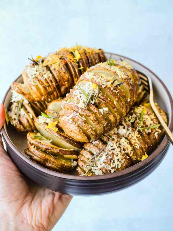 hasselback russet potatoes with rosemary, parmesan and garlic in bowl