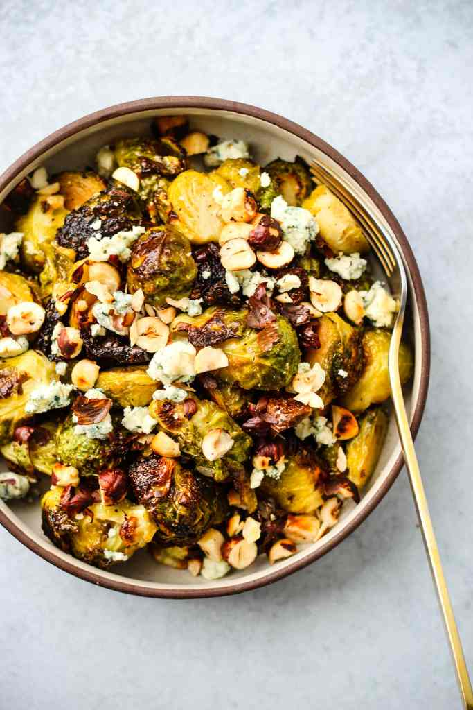 honey and garlic roasted brussels sprouts topped with blue cheese and hazelnuts in a bowl