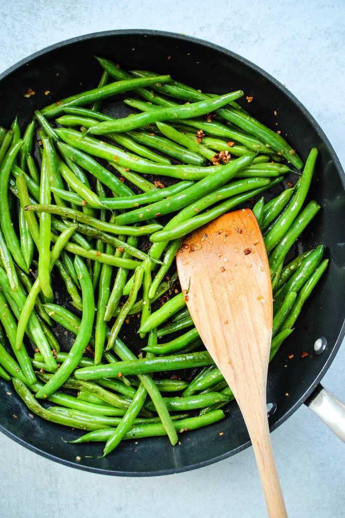 green beans sauteed in garlic on frying pan