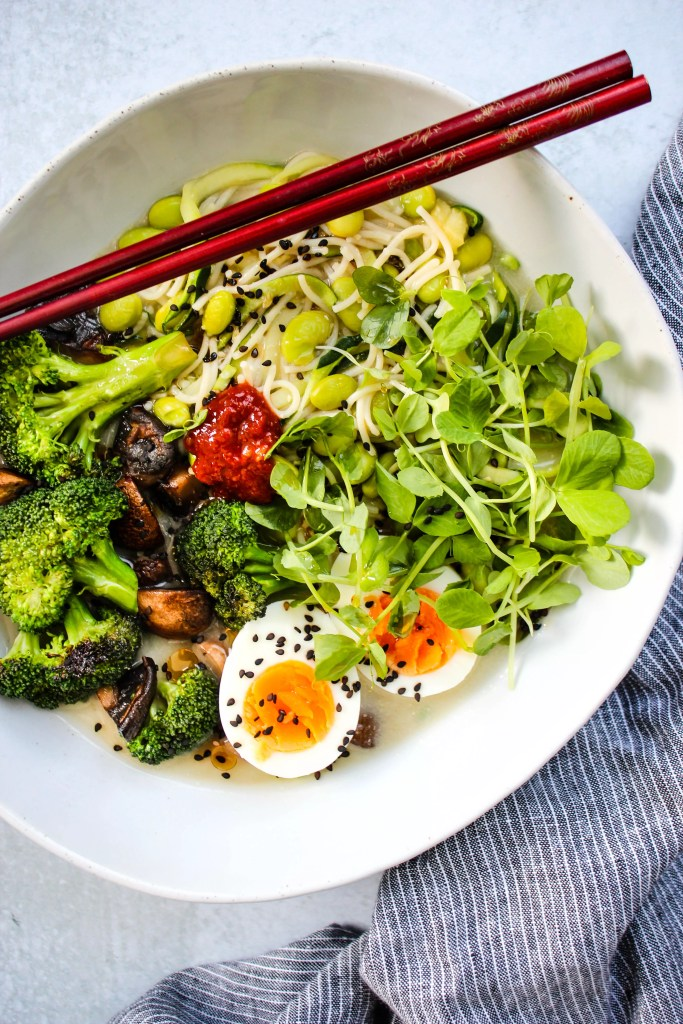 homemade miso ramen noodle soup with broccoli, mushrooms, eggs, and microgreens in white bowl