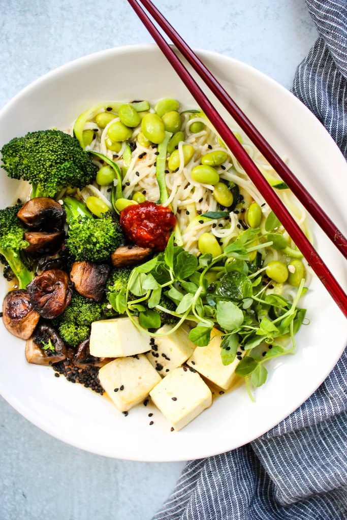 homemade miso ramen noodle soup with broccoli, mushrooms, tofu, and microgreens in white bowl