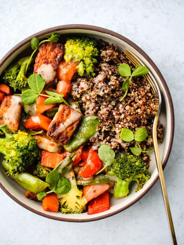 bowl of tempeh and vegetable stir-fry with quinoa and coconut milk sauce
