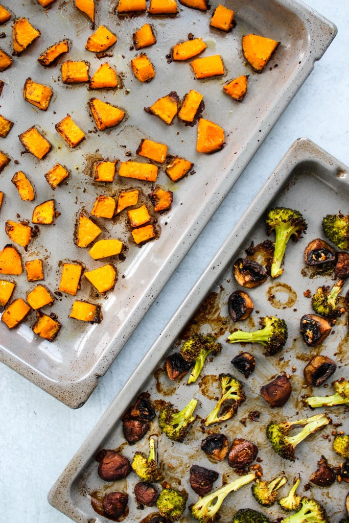 roasted butternut squash, broccoli, and mushrooms on two baking sheets