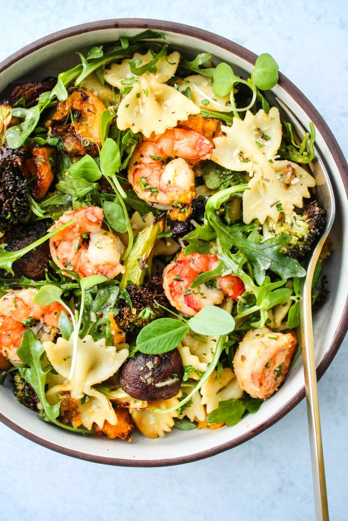 winter pasta salad with roasted butternut squash, mushrooms, broccoli, arugula, and shrimp in a bowl