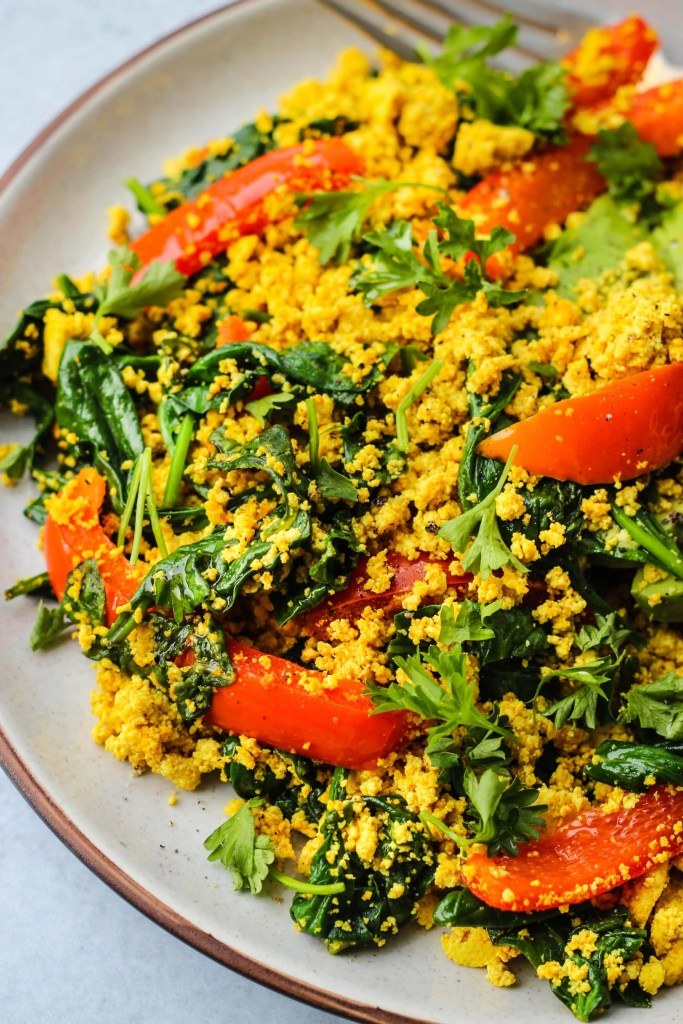 curry tofu scramble with red bell peppers and spinach on a plate