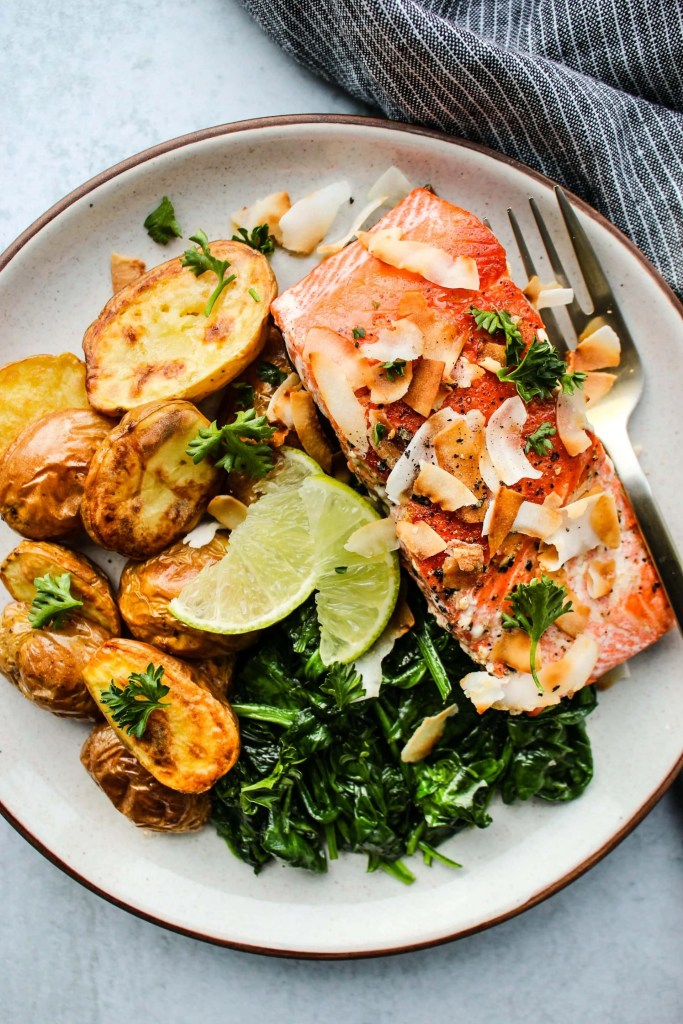 white plate with salmon fillet, potatoes, spinach, coconut, and lime