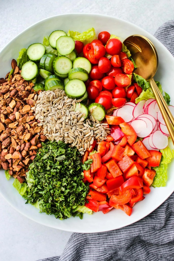 white bowl of chopped vegetables, nuts, and seeds