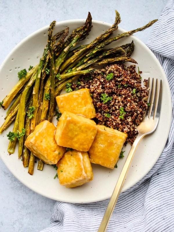 white bowl with crispy baked tofu, asparagus, quinoa