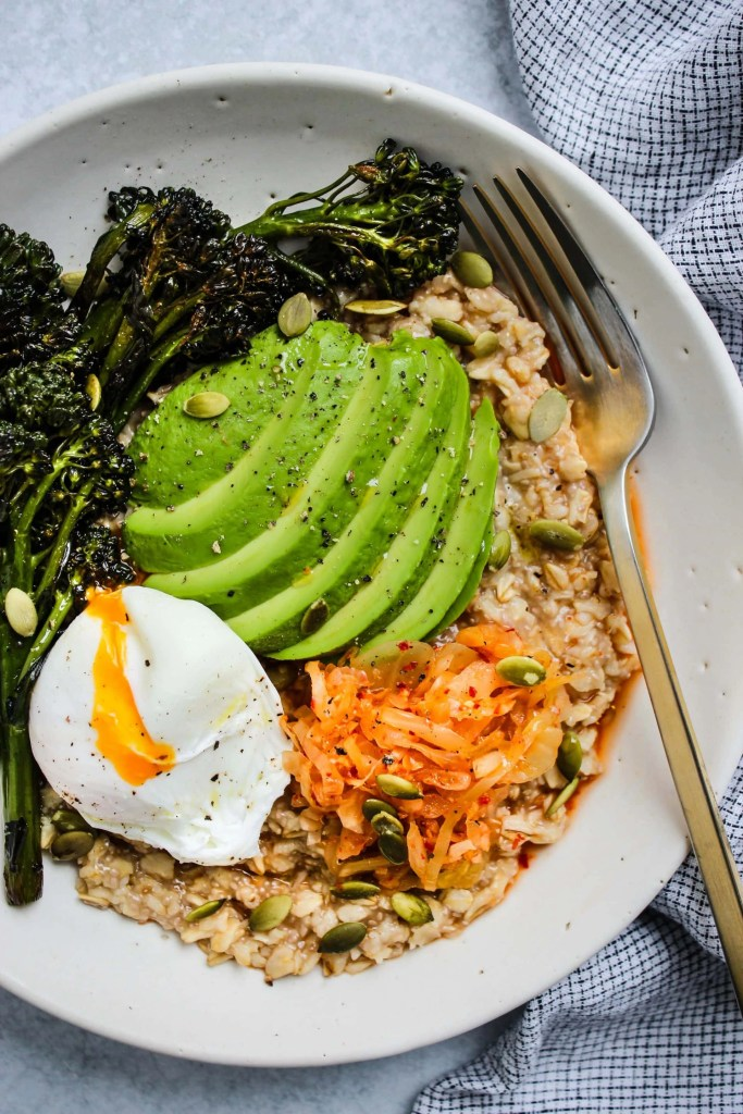 overhead shot of savoury oatmeal with poached egg, kimchi, avocado in white bowl