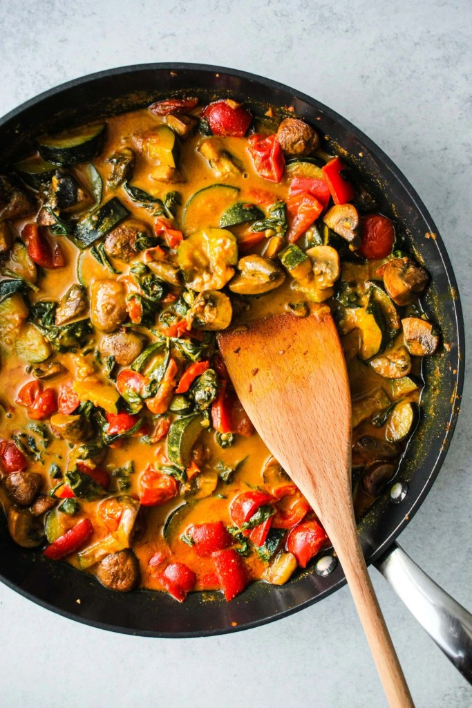 black pan with coconut curry and chopped zucchini, mushrooms, tomatoes, spinach stir fry