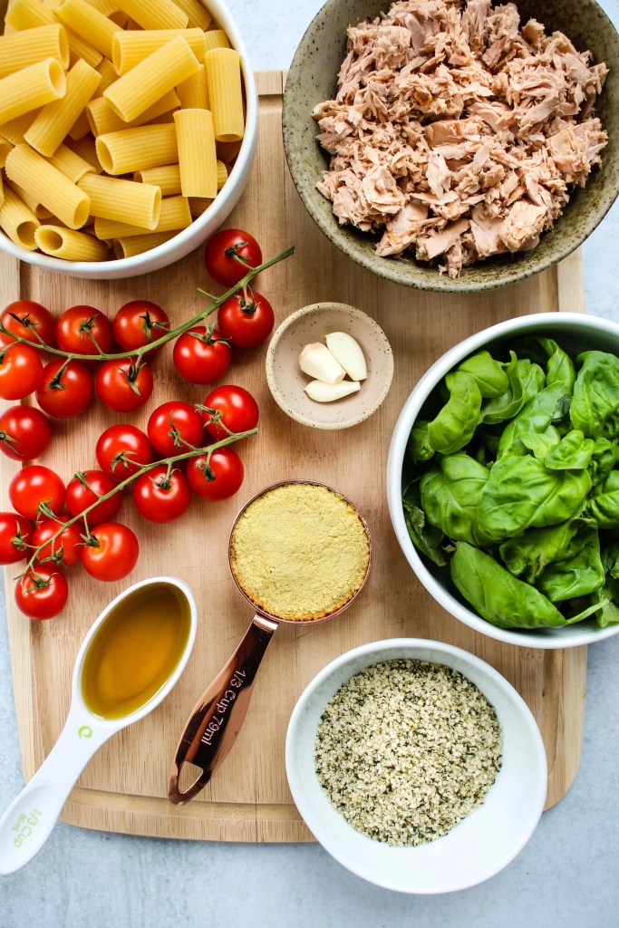 wood cutting board with bowls of pasta, canned tuna, basil, hemp seeds, nutritional yeast, garlic, olive oil, and vine of cherry tomatoes