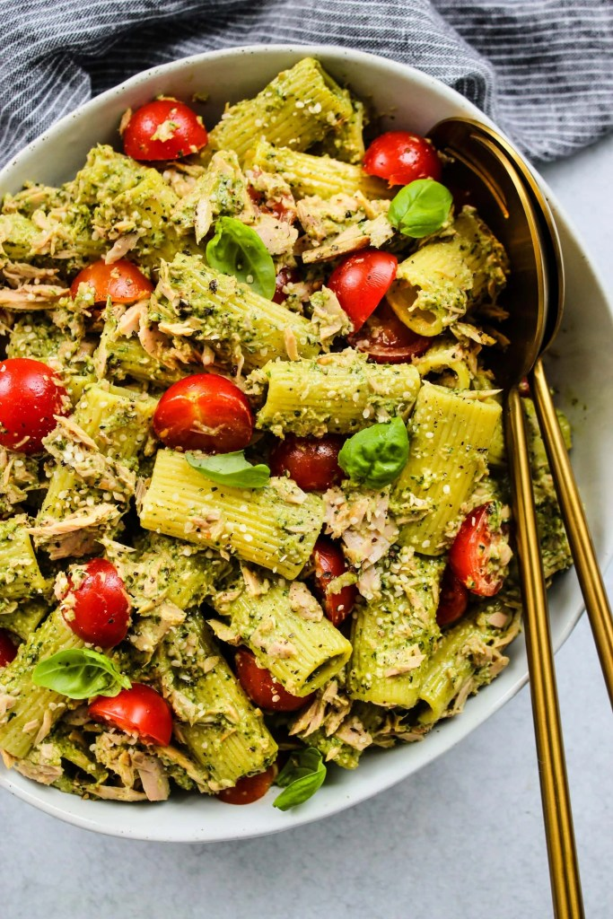 overhead shot of large white bowl with tuna pasta salad, pesto, cherry tomatoes and gold spoons