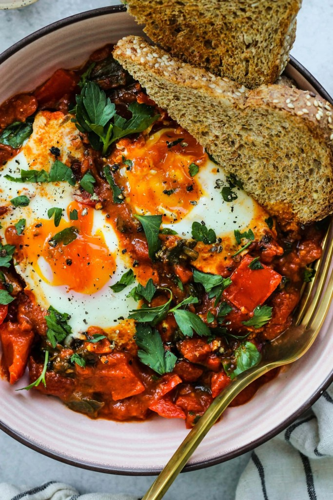 coconut curry shakshuka with two runny eggs in a pink bowl with two slices of toast