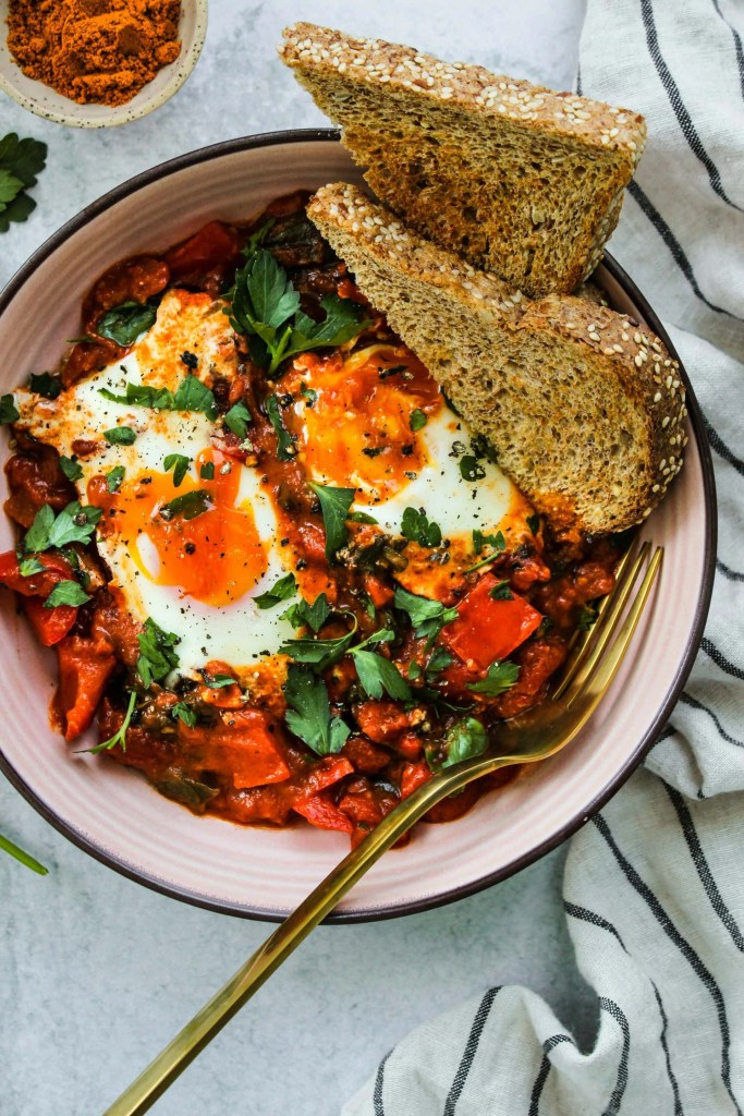 overhead shot of coconut curry shakshuka with two runny eggs in a pink bowl with two slices of toast and striped dishcloth