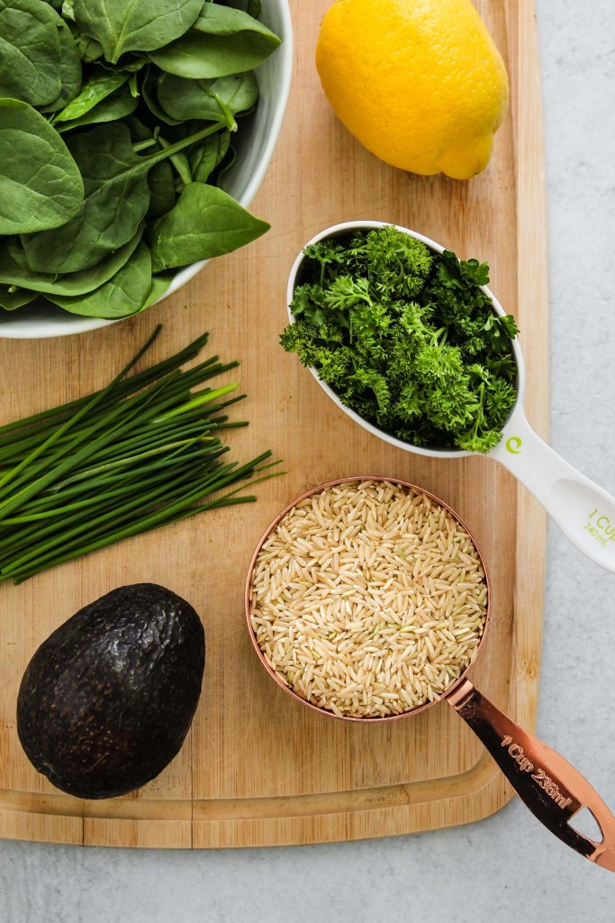 wood cutting board with cups of spinach, parsley, brown rice, avocado, chives, and lemon
