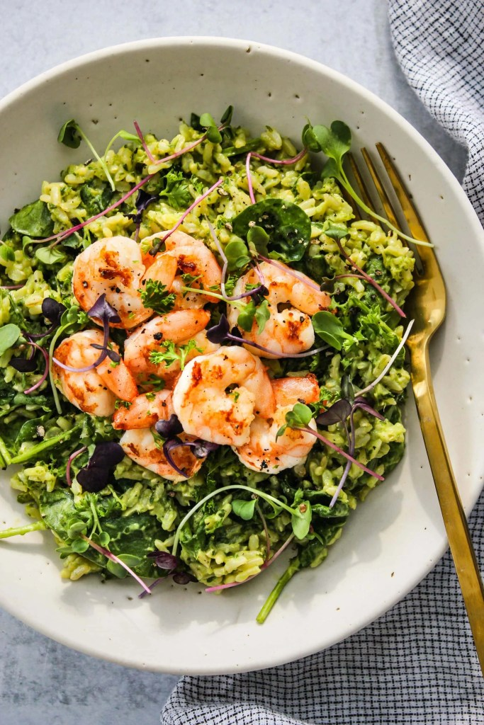 closeup of white bowl with green goddess rice and shrimp, gold fork
