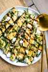 light blue plate with grilled zucchini slices topped with crumbled goat cheese, basil and honey and golden serving spoons