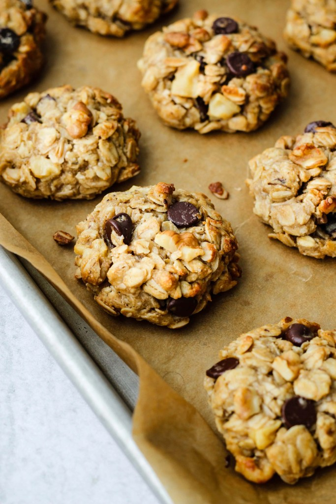 side angle of parchment lined baking dish with tahini oatmeal cookies
