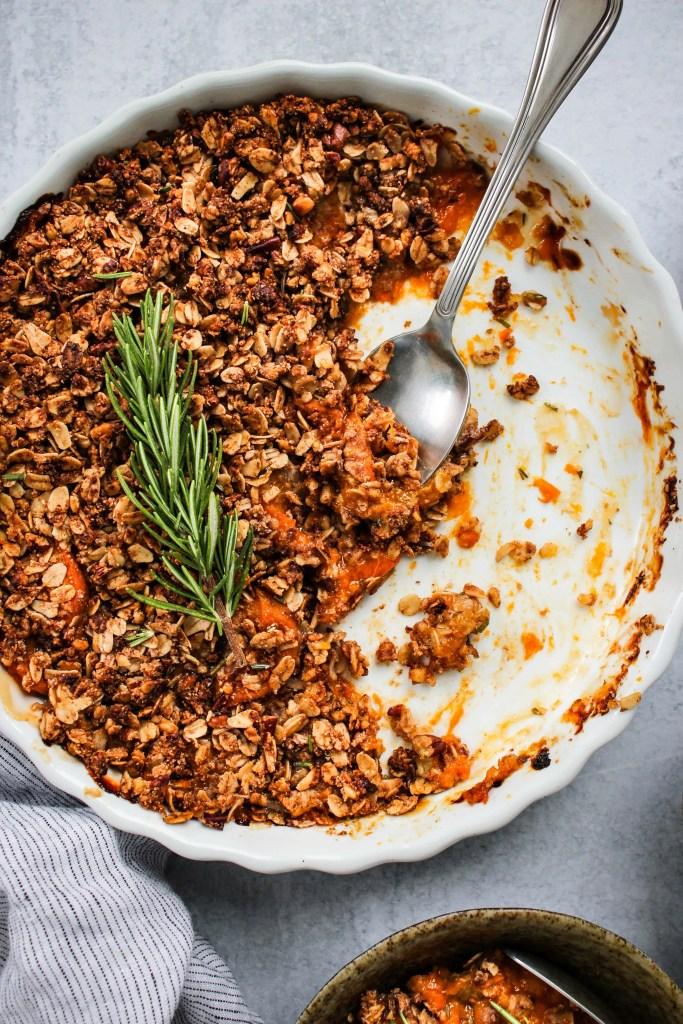closeup half eaten rosemary apricot crisp in white baking dish