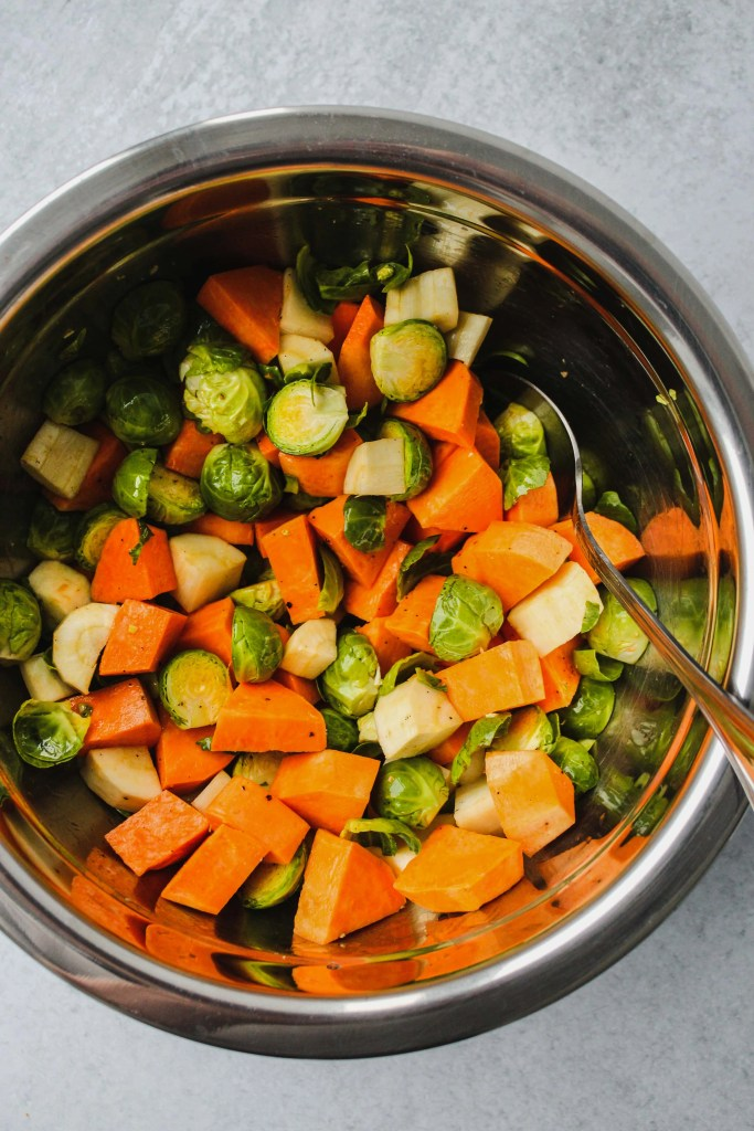 overhead photo of metal mixing bowl with chopped sweet potatoes and brussels sprouts inside