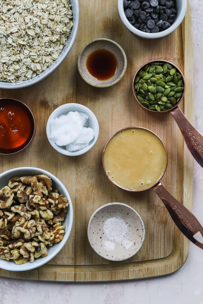 overhead photo of wood cutting board with bowls of granola ingredients on top