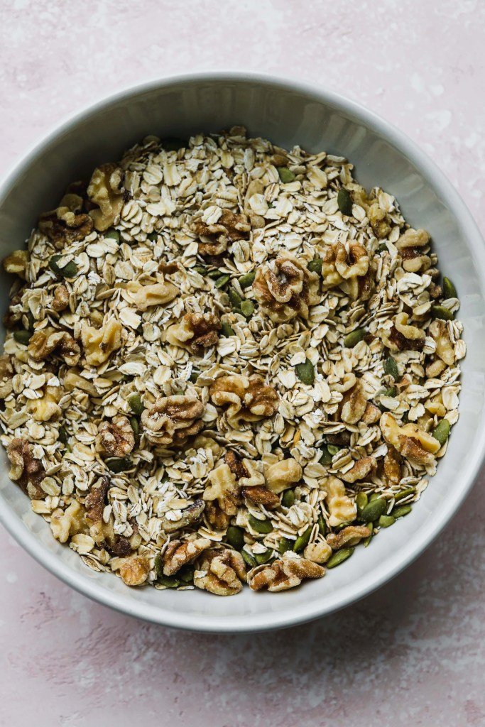 overhead photo of large white bowl with oats, walnuts, and pumpkin seeds mixed together