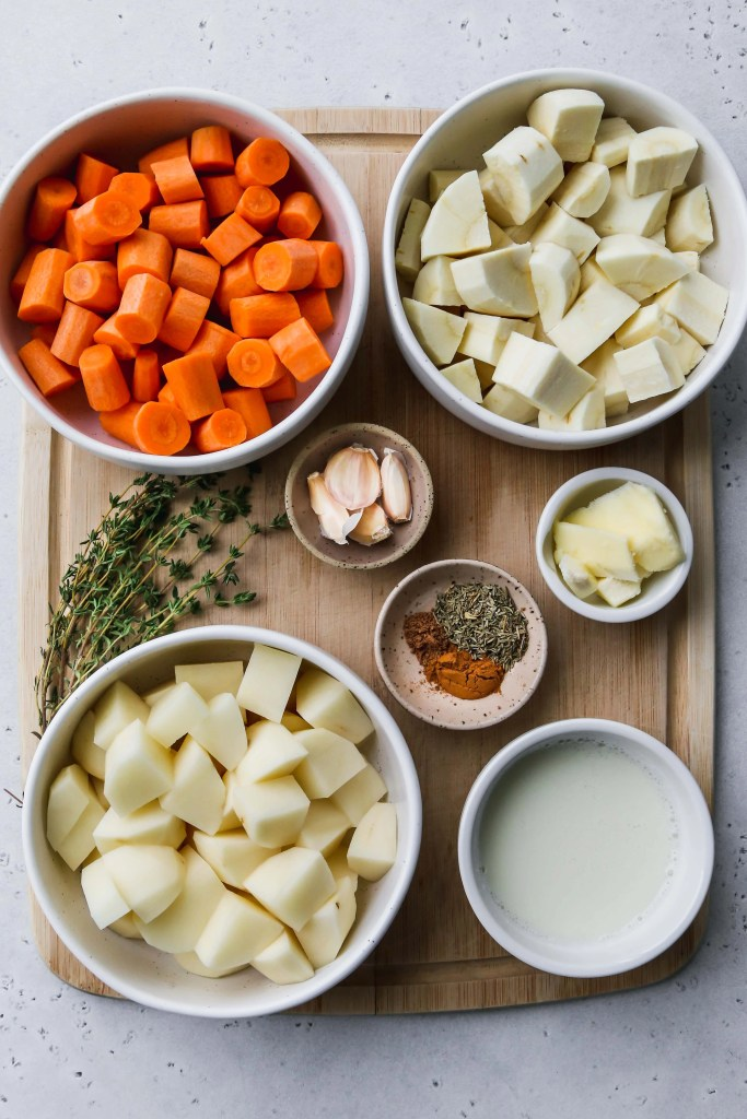 overhead photo of wood cutting board with bowls of chopped carrots, parsnips, potatoes, and other ingredients to be cooked
