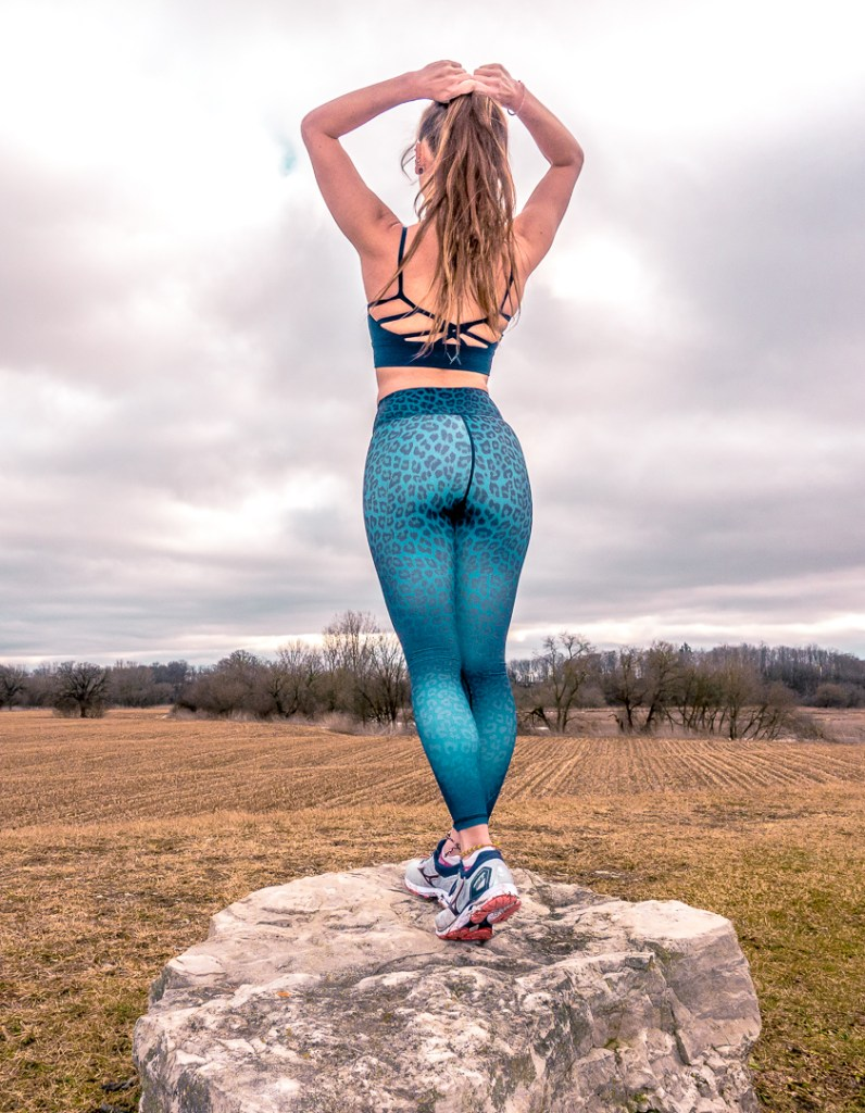 Picture of me standing on a rock wearing leggings and a sports bra. This is an example of fitness content I can produce