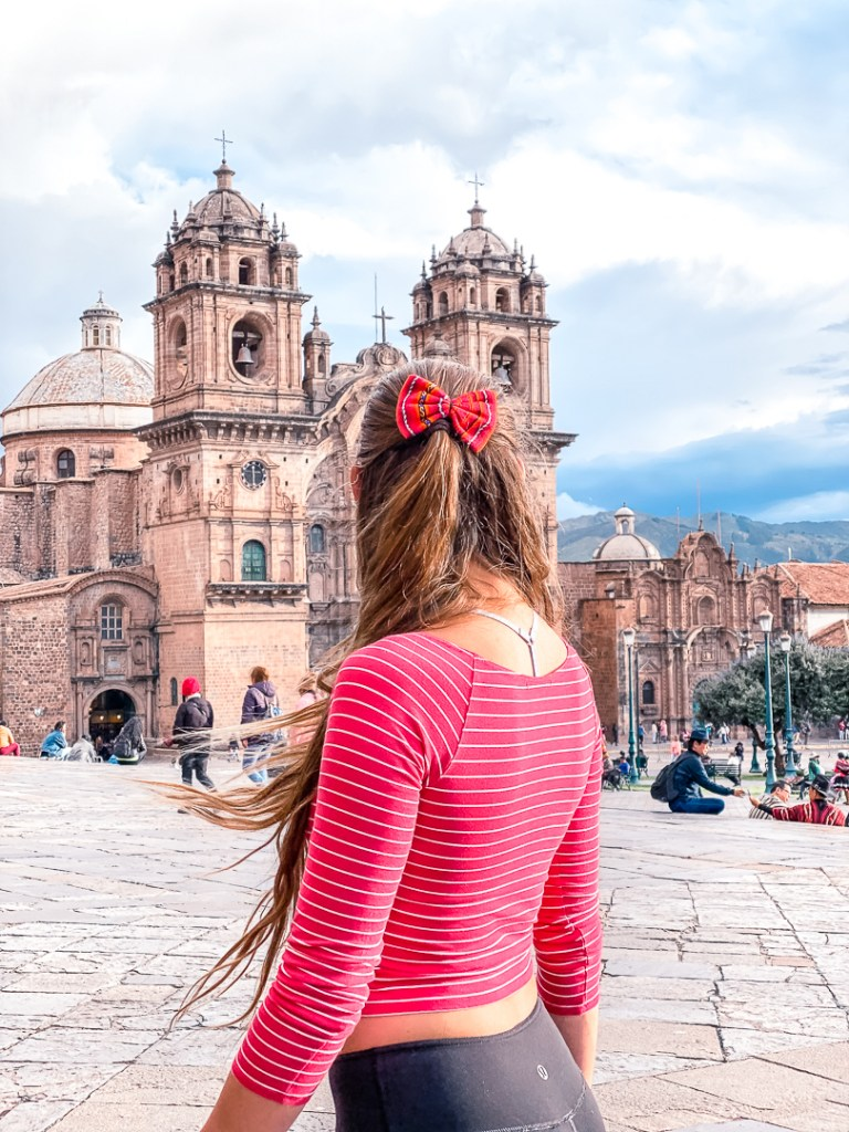 Girl with a red shirt and red bow looking at one of the churches in Cusco's plaza de armas