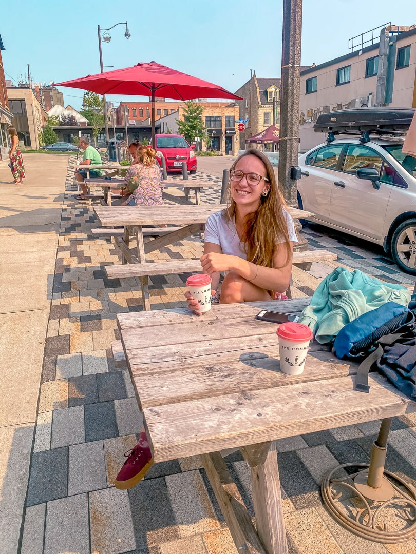sitting at the picnic tables outside of the common a guelph coffee shop