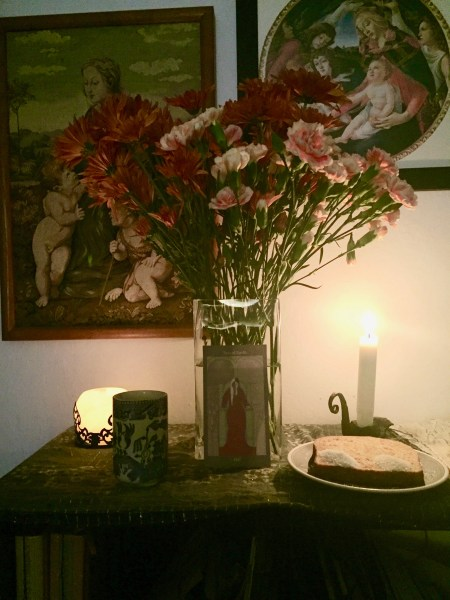 An altar with a an image of the Goddess Hel, a vase of flowers, two candles, a glass of water, and a small plate with a slice of bread on which is sprinkled salt and sugar.