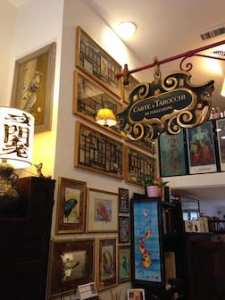 Interior of Il Meneghello shop, showing art-covered walls.