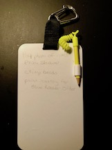 A small white plastic slate, suspended from a black fabric tab held by a silver carabiner. A yellow pencil is attached to the slate by means of a yellow cord. The slate has three notes written on it as example text.