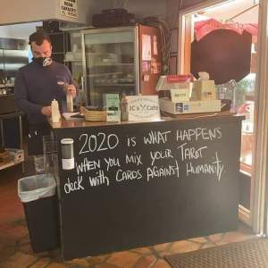 "A photo of a man standing behind the counter at a cafe. The chalkboard at the front of the counter reads, ""2020 is what happens when you mix your Tarot deck with Cards Against Humanity""."