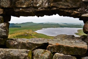 View over Hadrian's wall, Housesteads, Northumberland through a stone wall